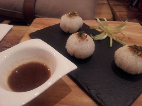 Adobo rice balls: sticky rice filled with chicken adobo, sprinkled with crunchy garlic and served with adobo sauce